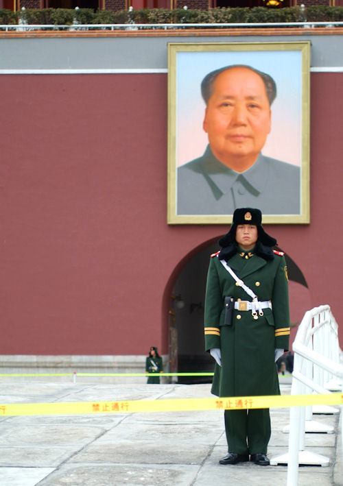 Soldier standing in Tiananmen Square in front of the famous portrait of Mao Zedong